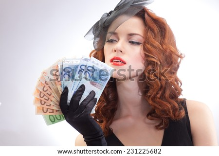 Portrait of a beautiful girl in a retro style in black dress with euro banknotes in the hands