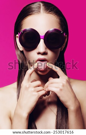 Portrait of a beautiful girl in glasses on a pink background stuck out her tongue - stock photo