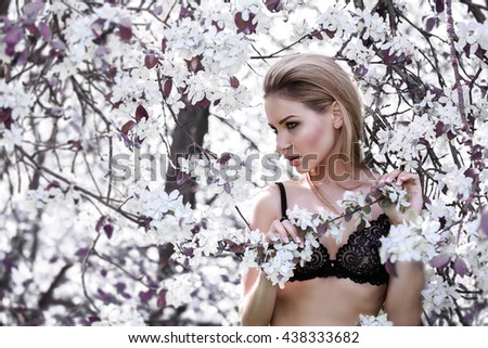Portrait of a beautiful girl in lingerie on wood background with flowers - stock photo