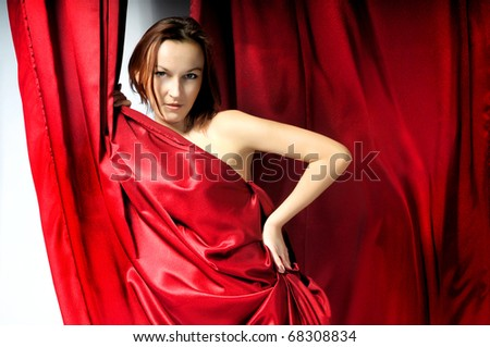 portrait of a beautiful girl in red satin fabric