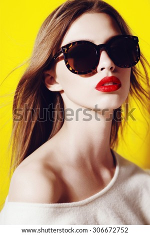 Portrait of a beautiful girl in sunglasses in the studio on a yellow background - stock photo