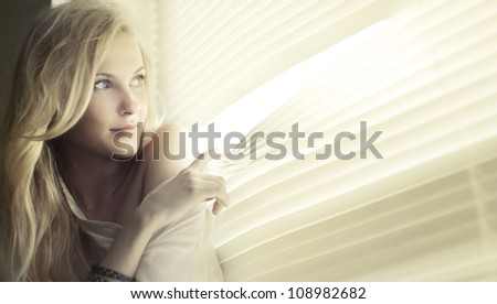 portrait of a beautiful girl in the window - stock photo