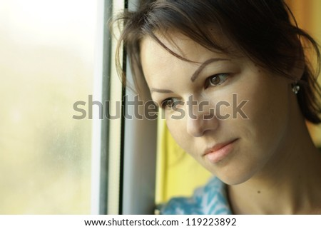 portrait of a beautiful girl looking out the window