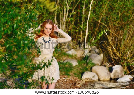 portrait of a beautiful girl on the bank of the river at sunset outdoor
