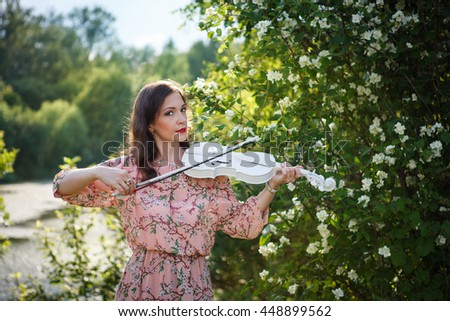 Portrait of a beautiful girl playing the violin in nature