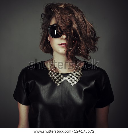 portrait of a beautiful girl posing in a studio in a leather dress and sunglasses - stock photo
