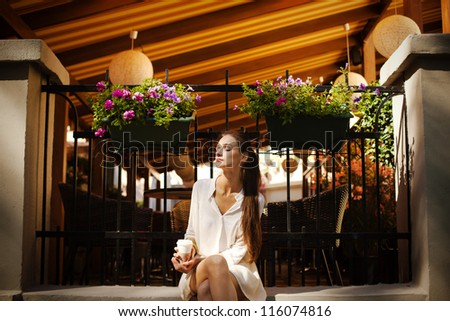 Portrait of a beautiful girl sitting next to the cafe on the street - stock photo