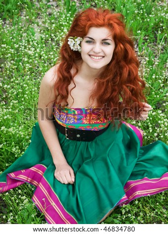 portrait of a beautiful girl sitting on green grass