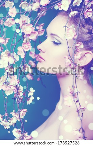 Portrait of a beautiful girl standing among the branches of cherry blossoms. Spring. - stock photo