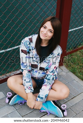 Portrait of a beautiful girl wearing roller skates, sitting on the street, looking at camera and smiling. Outside - stock photo