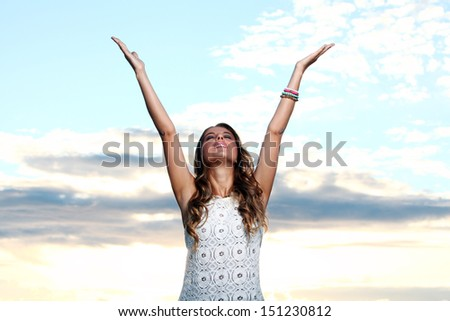 Portrait of a beautiful girl who is waving her hands happily by the sea - stock photo