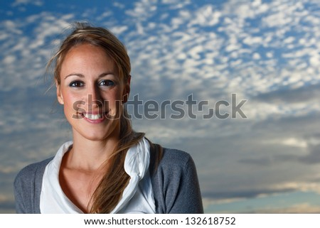 Portrait of a beautiful girl with a background of clouds - stock photo