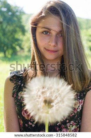 portrait of a beautiful girl with a flower in her hand against the background of the garden