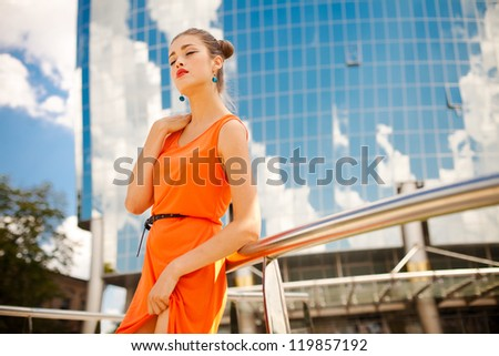 Portrait of a beautiful girl with a professional makeup and stylish clothes, walking around the city - stock photo