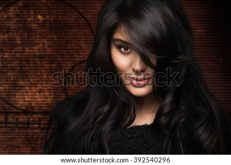 Portrait of a beautiful girl with black hair on a brown background - stock photo