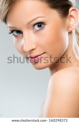 Portrait of a beautiful girl with blonde hair who is posing with her shoulders naked over a bright background - stock photo