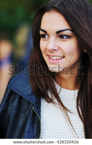 portrait of a beautiful girl with long hair in a black shirt smiling