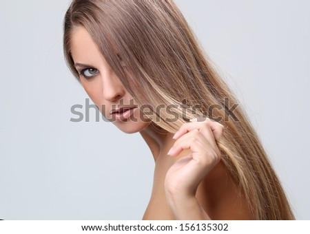 Portrait of a beautiful girl with makeup and naked shoulders who is posing