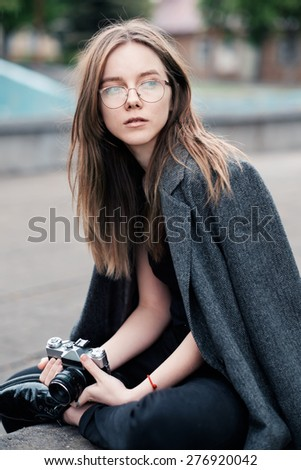 portrait of a beautiful girl with the camera hipster in town - stock photo