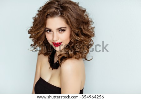 Portrait of a beautiful glamorous brunette with curly hair and bright makeup with red lipstick, close-up, beauty - stock photo