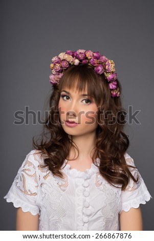 Portrait of a beautiful glamorous girl in a white blouse with a wreath of flowers on head, in the Studio on a dark background - stock photo