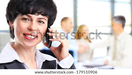 portrait of a beautiful happy brunette woman or businesswoman in her thirties talking on her cell phone