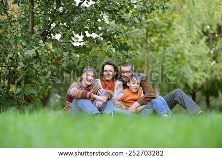 Portrait of a beautiful happy family sitting in autumn park - stock photo
