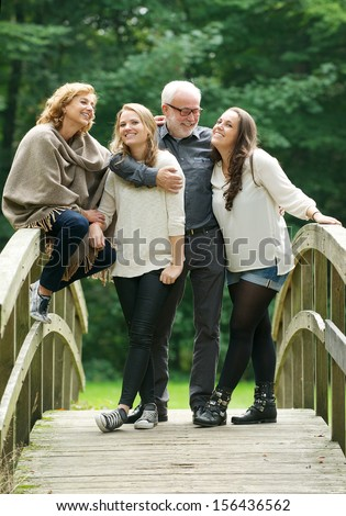 Portrait of a beautiful happy family standing together in a bridge in the woods - stock photo