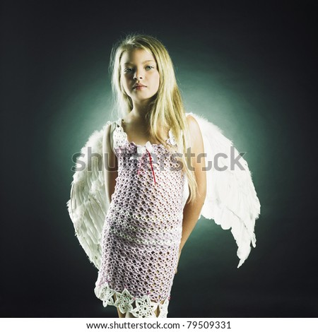 Portrait of a beautiful happy girl with angel wings - stock photo