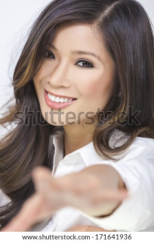 Portrait of a beautiful happy sexy young Chinese Asian woman or girl reaching her hand to the camera - stock photo