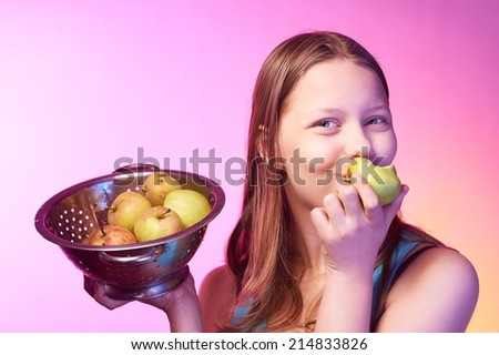 Portrait of a beautiful happy teen girl holding a colander full of apples and eating an apple - stock photo