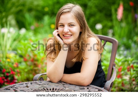 Portrait of a beautiful happy teenage high school senior girl sitting in a summer garden - stock photo