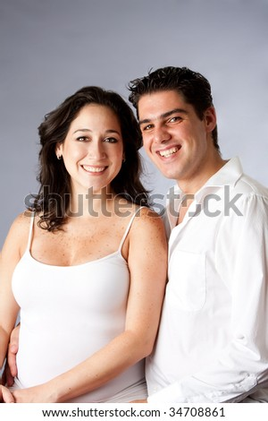 Portrait of a beautiful happy young couple smiling dressed in white, isolated - stock photo