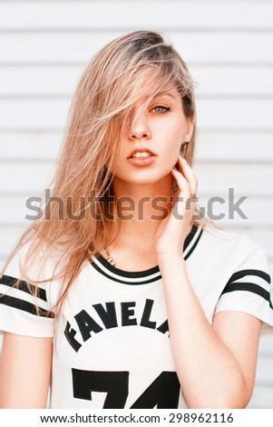 Portrait of a beautiful hipster girl near wooden wall.