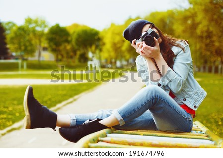 portrait of a beautiful hipster girl with a camera taking photos and sitting on a children's slide in the park - stock photo
