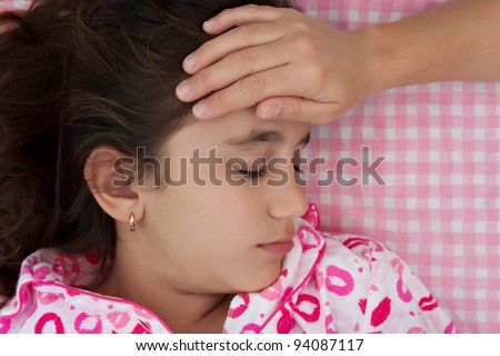 Portrait of a beautiful hispanic girl sick with fever while a hand measures her temperature - stock photo