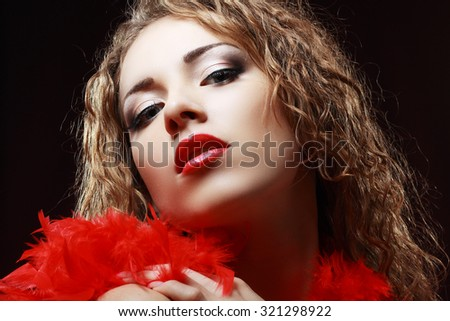 Portrait of a Beautiful Hot Girl With Long Curly Hair with red feather boa