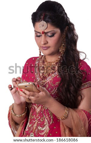 portrait of a beautiful Indian bride using cell phone  - stock photo