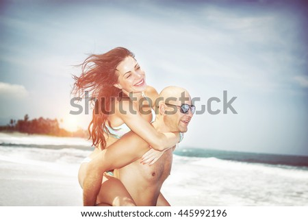 Portrait of a beautiful joyful couple having fun on a beach in bright sunny day, man holding his pretty girlfriend on piggyback, happy summer vacation - stock photo