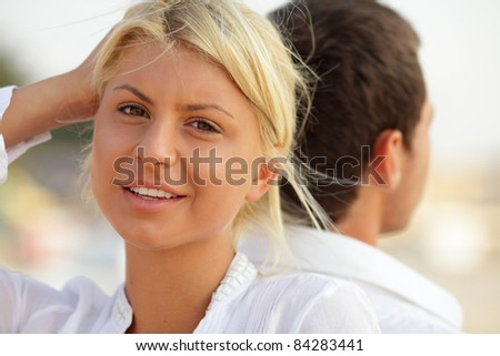 Portrait of a beautiful lady at the beach with her boyfriend at her back - stock photo