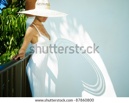 Portrait of a beautiful lady in a straw hat on the balcony - stock photo