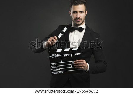 Portrait of a beautiful latin man with tuxedo and holding a clapboard - stock photo