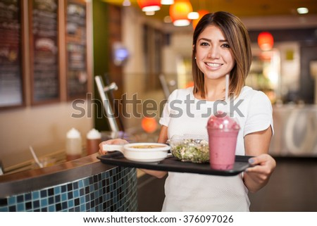 Portrait of a beautiful Latin woman with a tray full of food at a cafeteria - stock photo