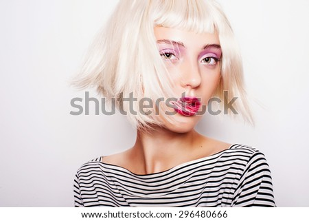Portrait of a beautiful laughing blonde girl in a striped dress in the studio on a white background
