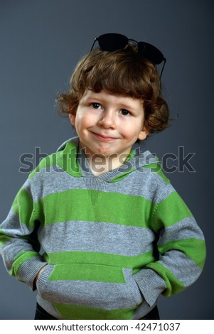 Portrait of a beautiful little fashionable boy holds a  hands in his pocket, gray background