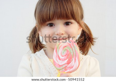 Portrait of a beautiful little girl holding a big round swirl lollipop