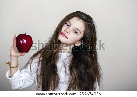 Portrait of a beautiful little girl holding a red apple, isolated on white background - stock photo