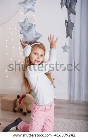 Portrait of a beautiful little girl in a in earmuffs in the interior with Christmas decorations. Girl grabs and catches toy star - an element of a Christmas decor - stock photo