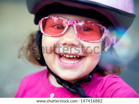 portrait of a beautiful little girl in a pink bicycle helmet and goggles - stock photo
