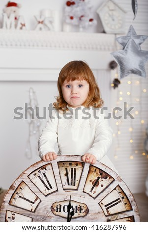 Portrait of a beautiful little girl in a white dress in the interior with Christmas decorations. Baby girl with big clock dial - stock photo